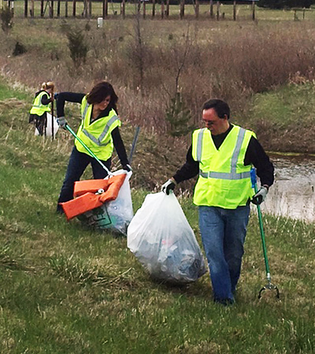 Three individuals picking up trash