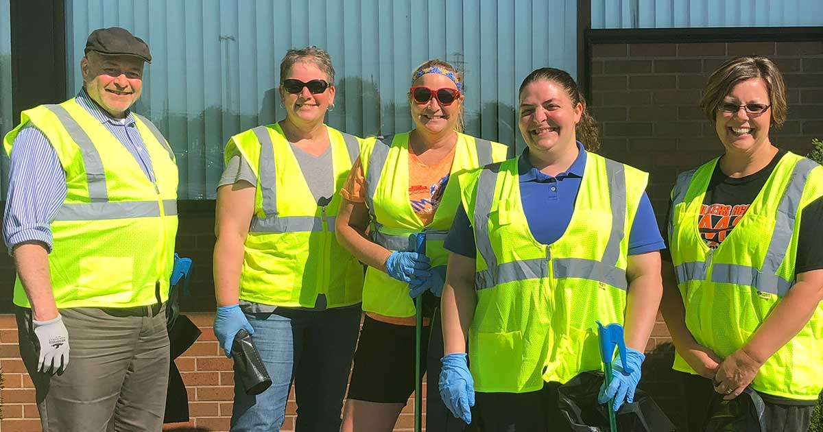 Five DCECU employees wearing high-visibility jackets and work gloves stand and smile in front of the DCECU building.
