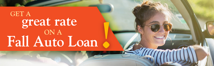 Get a great rate on a Fall Auto Loan! A smiling woman wearing sunglasses looks back at the viewer while riding in the passenger seat of a convertible in the evening sun.