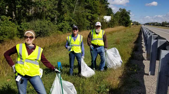 Three DCECU employees smile for a picture wearing high-visibility jackets as they clean up waste next to US-10