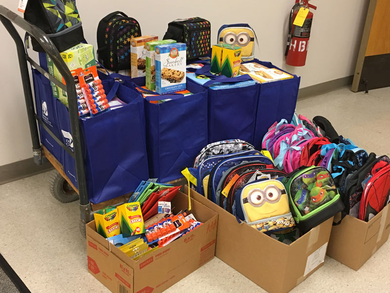 A push cart filled with fabric shopping bags full of various food items and art supplies and boxes on the floor full of childrens' backpacks for donation