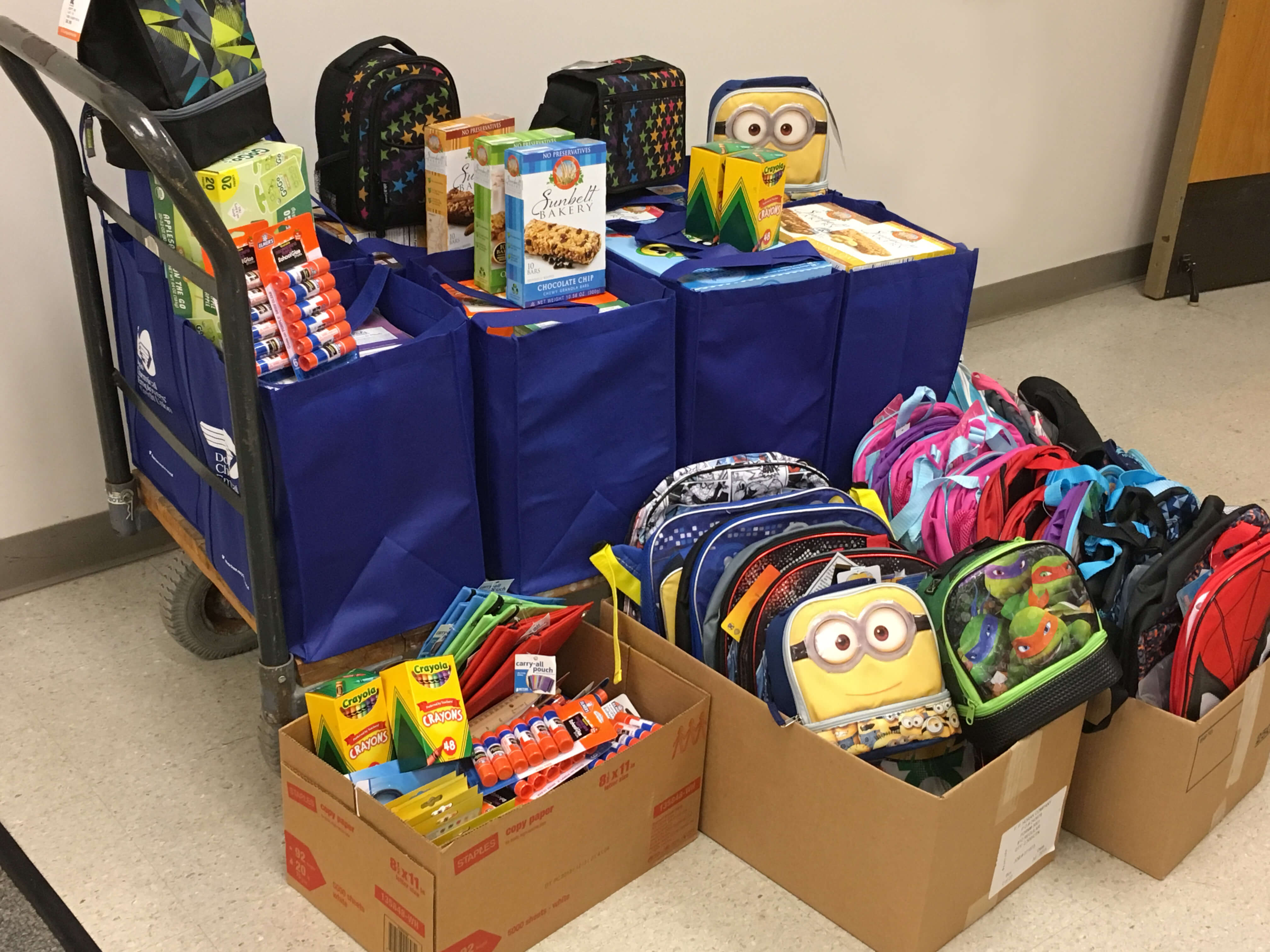 An Image of a wheeled cart filled with DCECU fabric bags full of children's school supplies and snacks