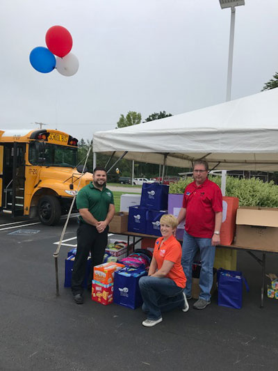 Two men and a woman pose in front of a tent with a table full of donations for children with a bus in the background and red, white, and blue balloons