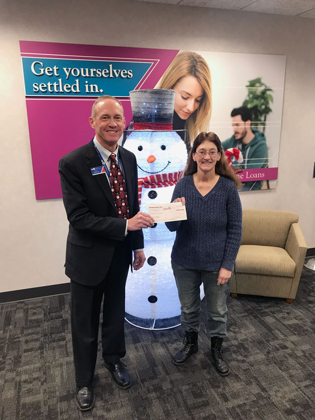 "Ken Roznowski (VP of Finance) hands a check to Jinell Schwerin in front of a lighted statue of a snowman and a poster in the background that says ""Get yourselves settled in. Home Loans"""