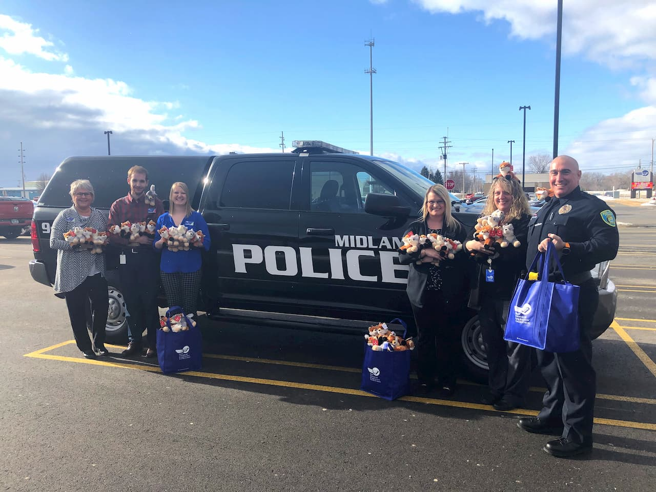 DCECU employees hold bags full of plush toys while standing in front of a police SUV with MPD Community Relations Officer Paul McDonald