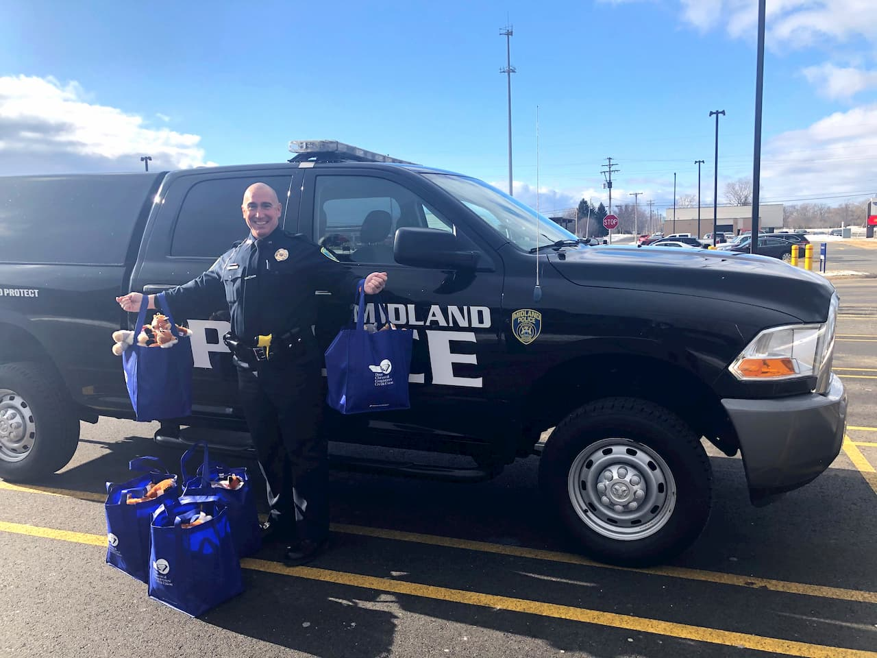 MPD Community Relations Officer Paul McDonald smiles in front of a police SUV while holding bags of plush animal toys for children
