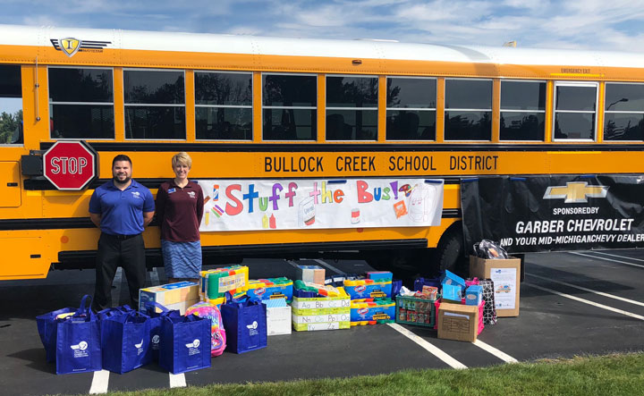 DCECU employees stand in front of a yellow Bullock Creek School District bus surrounded by childrens' school supplies; attached to the bus is a banner that says, 'Sponsored by Garber Chevrolet and your Mid-Michgan Chevy Dealers.