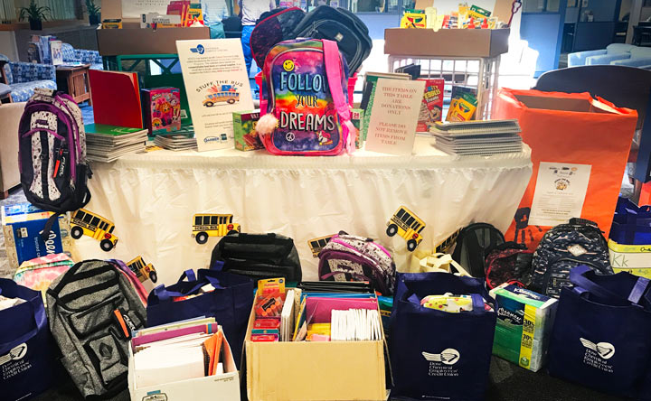 A table full of childrens' school supplies with a prominent rainbow backpack that says, 'Follow your dreams.'