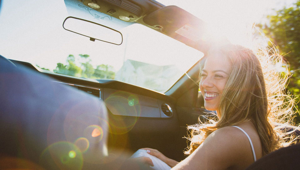 A woman smiles in the passenger seat of a convertible while riding in the evening sun
